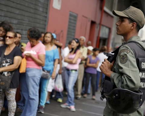 A Venezuelan soldier stands guard next to people forming a line to try to buy cornmeal flour and margarine at a pharmacy in Caracas