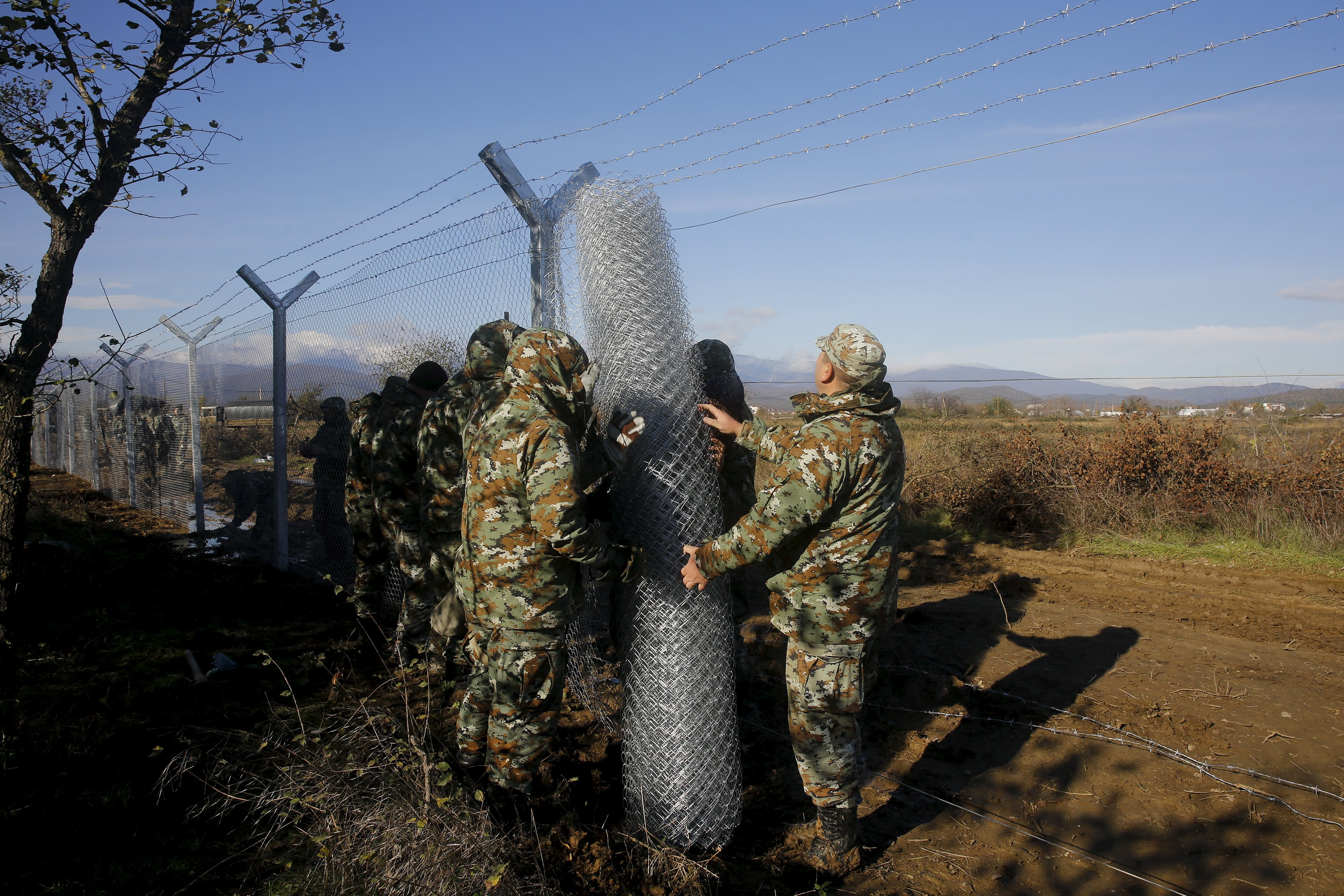 """Macedonian soldiers build up a metal fence at the Greek-Macedonian border near the Greek village of Idomeni, November 28, 2015. Soldiers in Macedonia began erecting a metal fence on Saturday on the country's southern border with Greece, described by an official as a """"preventive"""" measure to better control the flow of migrants across the Balkans. Picture taken from the Greek side of the border. REUTERS/Yannis Behrakis"""