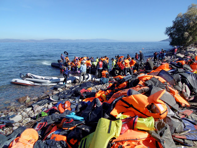 Πρόσφυγες και μετανάστες φτάνουν με φουσκωτή βάρκα στην Σκάλα Συκαμνιάς της Λέσβου,  που είναι καλυμμένη από σωσίβια, την Τρίτη 3 Νοεμβρίου 2015. Περισσότερες από 7.000 μετανάστες και πρόσφυγες ήταν εγκλωβισμένοι, σύμφωνα με στοιχεία της Αστυνομικής Διεύθυνσης Λέσβου, σήμερα το πρωί, στο λιμάνι της Μυτιλήνης, αφού λόγω της απεργίας της ΠΝΟ δεν πραγματοποιείται από τα χαράματα χθες Δευτέρα κανένα δρομολόγιο, τακτικό ή έκτακτο, προς τον Πειραιά ή την Καβάλα.  Σήμερα, με την καλυτέρευση των καιρικών συνθηκών, ιδιαίτερα στη βόρεια Λέσβο, περνάν κατά πολλές εκατοντάδες άνθρωποι από τα απέναντι παράλια. Η αυξημένη αυτή ροή δείχνει ότι πιθανά ο αριθμός των εγκλωβισμένων στη Λέσβο μεταναστών και προσφύγων θα φτάσει τα δυσθεώρητα ύψη των αρχών του περασμένου Σεπτεμβρίου.  ΑΠΕ- ΜΠΕ/ ΑΠΕ-ΜΠΕ /ΣΤΡΑΤΗΣ ΜΠΑΛΑΣΚΑΣ