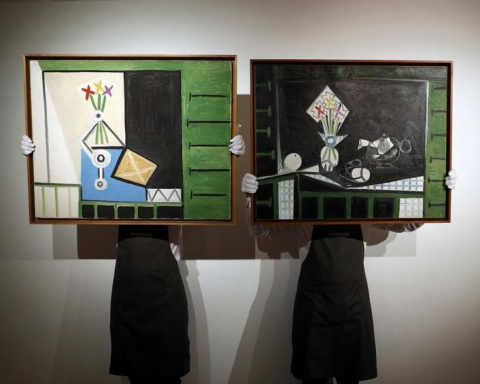 """Art handlers pose with """"Nature morte"""" and """"Nature morte aux volets verts"""" by Pablo Picasso at Christie's auction house in London"""